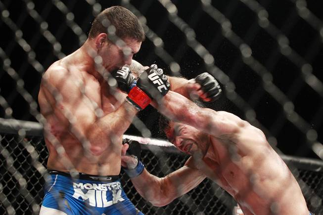 Chris Weidman gets hit with a left by Lyoto Machida during their fight at UFC 175 at the Mandalay Bay Events Center Saturday, July 5, 2014. Weidman won a unanimous decision to retain his middleweight belt.