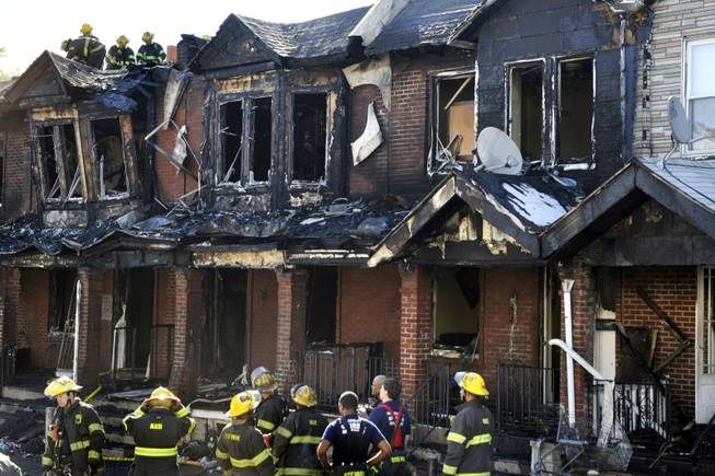 Firefighters work at a scene of a fire that that raced through a row of two-story homes in southwest Philadelphia on Saturday, July 5, 2014. The fire that killed three 4-year-olds and a baby, engulfing at least 10 houses, may have started in a couch on a porch, officials said.