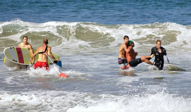 Two men carry a swimmer, second from right, after he was bitten by a great white shark, as lifeguards close in at left in the ocean off Southern California's Manhattan Beach on Saturday, July 5, 2014.