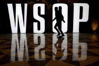 A man walks by a sign on the first day of the World Series of Poker main event Saturday, July 5, 2014 in Las Vegas. Players are vying for the $10 million first-place payout at the poker tournament. (AP Photo/John Locher)