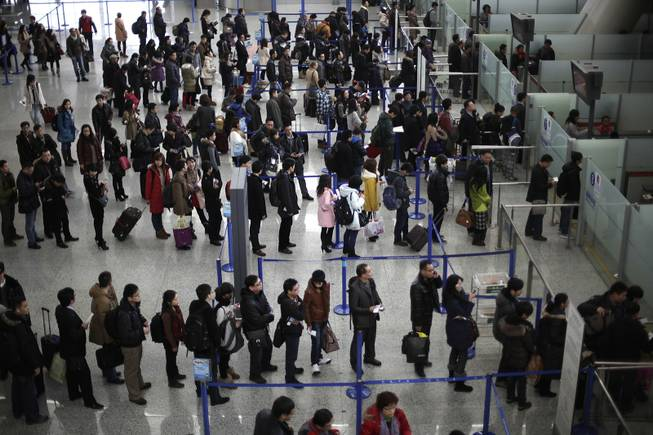 In this Jan. 20, 2012, file photo, passengers queue up for a security check at Pudong International Airport in Shanghai, China. The Transportation Security Administration is requiring passengers at some overseas airports that offer U.S.-bound flights to power on their electronic devices, the agency said Sunday, July 6, 2014. It says devices that won't power up won't be allowed on planes, and those travelers may have to undergo additional screening.