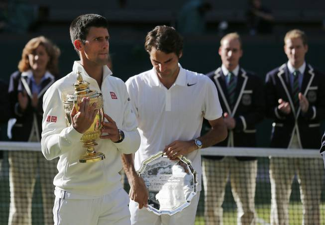 Novak Djokovic of Serbia, left, holds the trophy after defeating Roger Federer of Switzerland in the men's singles final at the Wimbledon All England Lawn Tennis Championships on Sunday, July 6, 2014, in London, England.