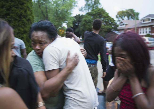 In this Saturday, July 5, 2014, photo, Georgia Utendahl, left, and Shanice Smith, right, grieve after learning that their family member was shot by police on Chicago's South Side. The Fourth of July weekend was a bloody one in Chicago, where at least nine people were shot to death and at least 60 others were wounded.