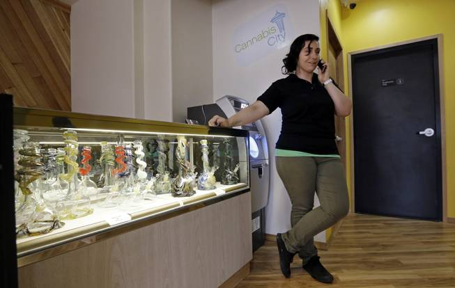 Cannabis City manager Amber McGowan takes the marijuana shop's first call, from a potential customer, days before the grand opening Wednesday, July 2, 2014, in Seattle. The store expects to begin selling pot Tuesday, July 8, the first day that recreational marijuana can legally be sold in Washington state and is expected to be the first licensed retailer in Seattle.