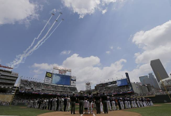 Military aircraft fly over Target Field during the national anthem as part of Military Appreciation Day before a baseball game between the New York Yankees and the Minnesota Twins in Minneapolis, Sunday, July 6, 2014.