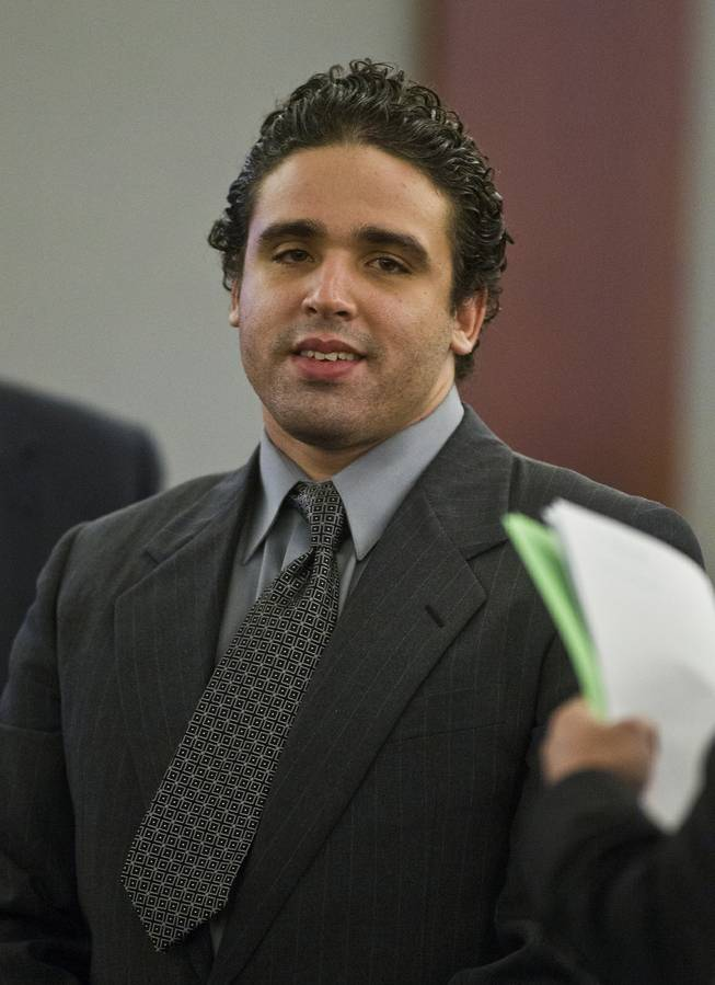 Joey Kadmiri smiles at jury members as they pass by during a break in his trial at the at the Regional Justice Center on Tuesday, July 8, 2014.