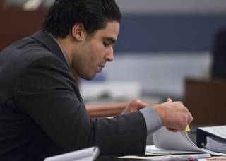 Joey Kadmiri looks through paperwork's his trial begins, he was  allegedly beat up by the Thunder From Down Under Male Revue dancers after trying to burglarize their locker room Tuesday, July 8, 2014.