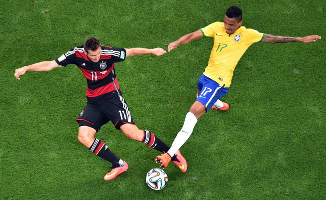 Germany's Miroslav Klose, left, and Brazil's Luiz Gustavo go for the ball during the World Cup semifinal soccer match between Brazil and Germany at the Mineirao Stadium in Belo Horizonte, Brazil, Tuesday, July 8, 2014. (AP Photo/Francois Xavier Marit, Pool)