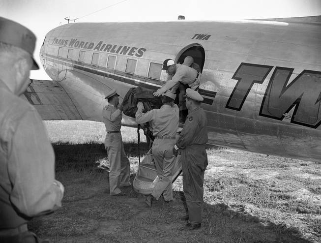 First of eight more bags containing portions of unidentified people who died in the crash of a TWA Constellation near here on Saturday, June 30, is loaded aboard a plane for flight to the coroner's office in Flagstaff in Grand Canyon, Arizona , July 3, 1956. Seven more bags are expected to be flown out from the crash where 70 died. This will complete the TWA search and four bags from the UAL crash are expected to be flown out.