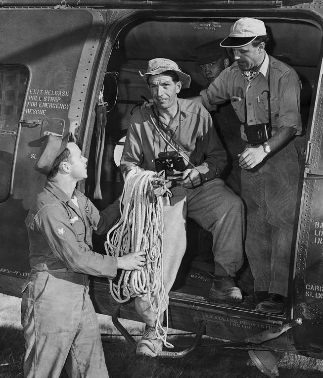 Two members of a Swiss mountain climbing team, who arrived in Grand Canyon, Arizona to assist in recovering bodies of victims of a UAL plane crash in this canyon on June 30, are handed a coil of rope by Spc/3 Robert Lee as they leave by helicopter for the wreck scene, July 6, 1956. From left are Lee, Anton Spinas, who will direct the team, and Max Stampfli, Swiss pilot.