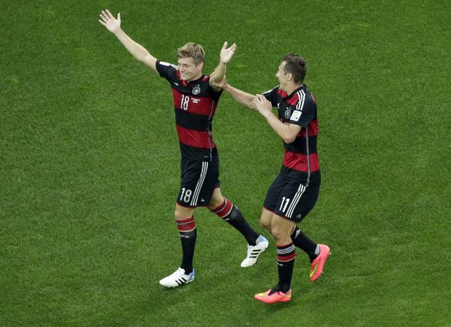 Germany's Toni Kroos, left, celebrates scoring his side's third goal with teammate Miroslav Klose during the World Cup semifinal soccer match between Brazil and Germany at the Mineirao Stadium in Belo Horizonte, Brazil, Tuesday, July 8, 2014.