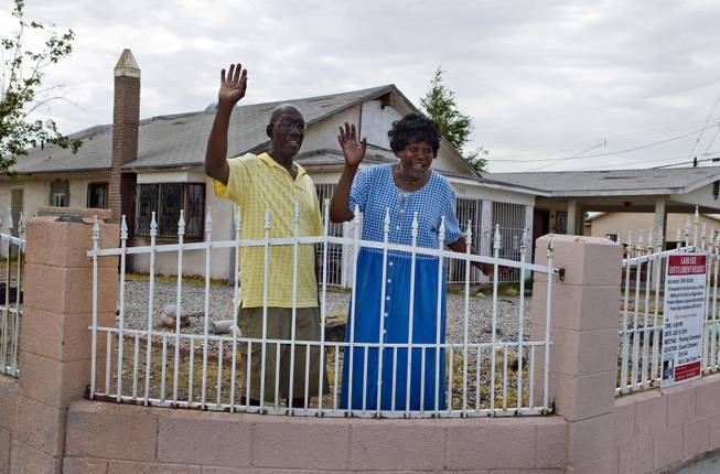 Stanton Wilkerson and Katherine Duncan wave to Metro Police Officer Gordie Bush as they stand outside the Harrison House on Wednesday, July 9, 2014. The home is where black entertainers and others stayed when Jim Crow-like laws ruled Las Vegas.