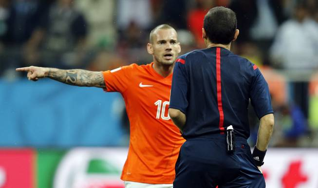 Netherlands' Wesley Sneijder argues with referee Cuneyt Cakir from Turkey during the World Cup semifinal soccer match between the Netherlands and Argentina at the Itaquerao Stadium in Sao Paulo, Brazil, Wednesday, July 9, 2014.