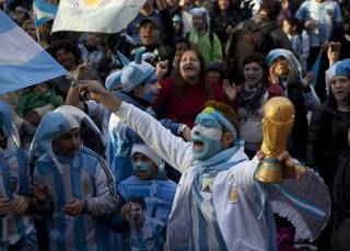 An Argentina soccer fan cheers while holding a replica of the World Cup trophy before a World Cup semifinal match between Argentina against Netherlands, on a street where an outdoor screen has been set for viewing, in Buenos Aires, Argentina, Wednesday, July 9, 2014.