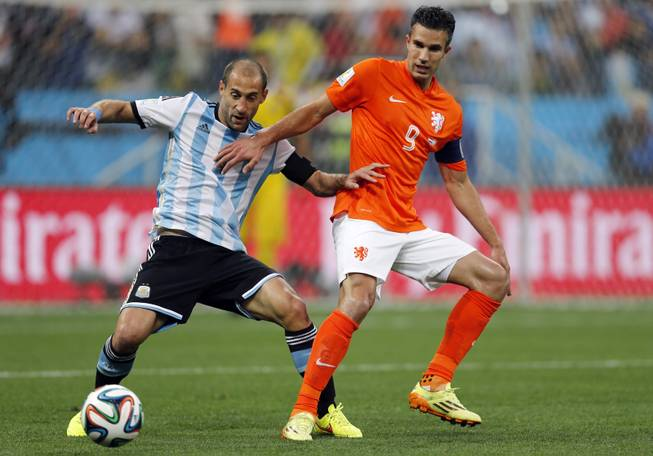 Argentina's Pablo Zabaleta, left, and Netherlands' Robin van Persie challenge for the ball during the World Cup semifinal soccer match between the Netherlands and Argentina at the Itaquerao Stadium in Sao Paulo, Brazil, Wednesday, July 9, 2014.