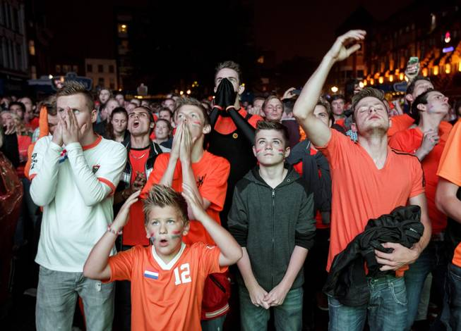 Soccer fans watch a live broadcast of the World Cup semifinal soccer match between Netherlands and Argentina on a giant screen in the center of Eindhoven, Netherlands, Wednesday, July 9, 2014. (AP Photo/Phil Nijhuis)