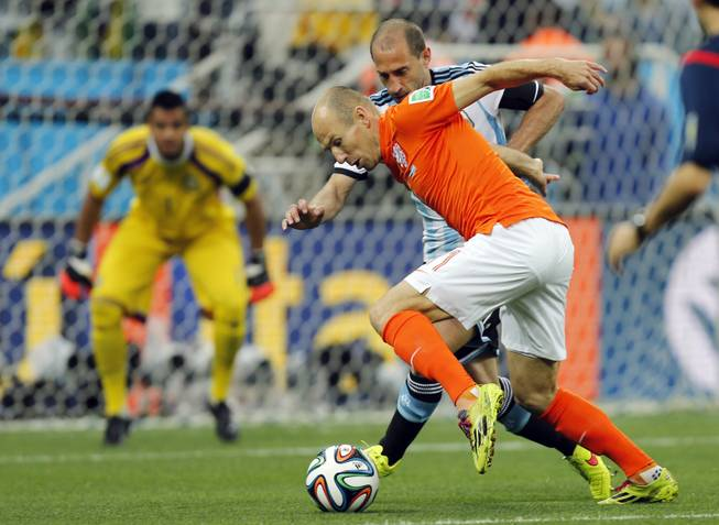 Netherlands' Arjen Robben, front, and Argentina's Pablo Zabaleta challenge for the ball during the World Cup semifinal soccer match between the Netherlands and Argentina at the Itaquerao Stadium in Sao Paulo, Brazil, Wednesday, July 9, 2014.