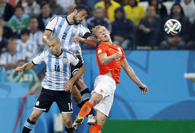 Netherlands' Dirk Kuyt, right, goes for a header with Argentina's Javier Mascherano, left, and Ezequiel Garay during the World Cup semifinal soccer match between the Netherlands and Argentina at the Itaquerao Stadium in Sao Paulo, Brazil, Wednesday, July 9, 2014.
