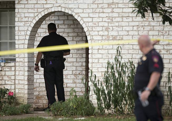 Law enforcement officers investigate the scene of a shooting Wednesday, July 9, 2014, in Spring, Texas. A Harris County Sheriff's Office statement says precinct deputy constables were called to a house about 6 p.m. Wednesday and found two adults and three children dead. Another child later died at a hospital.