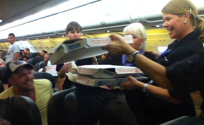 In this photo taken Monday, July 7, 2014, a Frontier Airlines flight attendant passes out pizza to passengers aboard a Denver-bound flight diverted to Cheyenne, Wyo. The airplane pilot treated his passengers to the pizza after they were diverted.