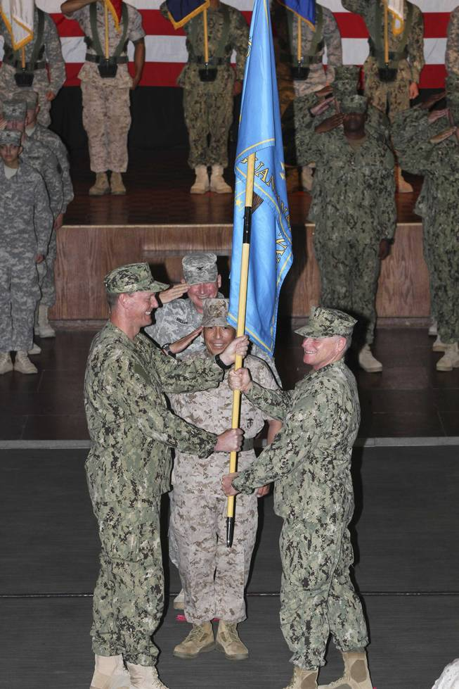 Rear Adm. Richard Butler hands the colors to Rear Adm. Kyle Cozad during a change-of-command ceremony at Joint Task Force Guantanomo on Thursday, July 10, 2014. Cozad, a Las Vegas native and 1981 graduate of Chaparral High School, took over command of the base in Cuba from Butler.