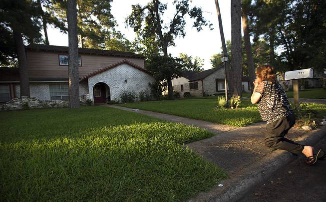 Patti Beller prays Thursday, July 10, 2014, in Spring, Texas, outside the home that was the scene of a multiple shooting the night before. The Harris County Sheriff's Office says Ronald Lee Haskell was booked Thursday on a capital murder/multiple murders charge and held without bond.