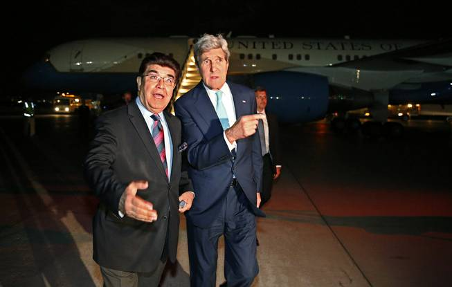 U.S. Secretary of State John Kerry, right, talks with Afghanistan's Ministry of Foreign Affairs chief of protocol Ambassador Hamid Siddiq, as Kerry arrives at Kabul International airport in Kabul, Friday July 11, 2014.
