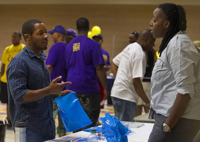 Attendees talk during a Stop the Violence event at the Pearson Community Center featuring local support agencies on Saturday, June 28, 2014.