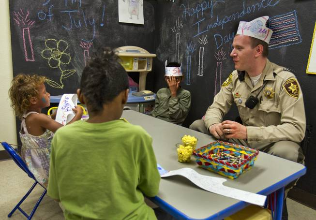 Metro Police Officer Gordie Bush joins Brooklyn, 3, Anthony, 6, and Christian Bannister, 8, in making paper and crayon hats at the Sherman Gardens Youth Center on Thursday, July 3, 2014.