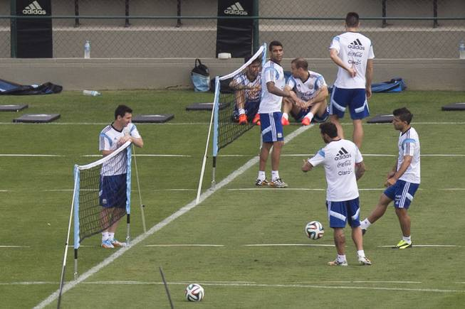 Argentina's Lionel Messi, left, talks to teammates Sergio Aguero, right, and Ezequiel Lavezzi, second right, during a training session in Vespesiano, near Belo Horizonte, Brazil, Friday, July 11, 2014. On Sunday, Argentina faces Germany for the World Cup final soccer match in Rio de Janeiro.