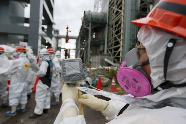 A Tokyo Electric Power Co.'s staff member measures the radiation in the air as workers prepare materials which will be used to create a frozen underground wall to surround the crippled reactor buildings at Tokyo Electric Power Co.'s Fukushima Daiichi Nuclear Power Plant in Okuma, Fukushima Prefecture, northeast of Tokyo, Japan, Wednesday, July 9, 2014. TEPCO plans to build a frozen wall around the buildings of Units 1 to 4 at the tsunami-devastated nuclear power plant to stop radiation-contaminated water from flowing to the sea. TEPCO has been struggling with massive amounts of toxic water as the operator continues to pump water into three reactors to keep them cool. The plant suffered meltdowns at three of its six reactors after a tsunami swept through the facilities in March 2011.