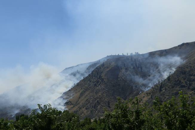 Smoke rises from the area of a wildfire near Entiat, Wash., on Friday, July 11, 2014. Several hundred firefighters worked Friday to contain the fire, which has burned grass and brush across 32 square miles in central Washington.