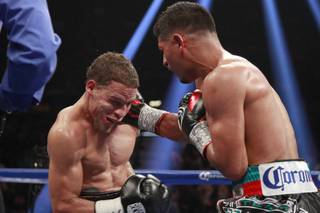 Jonathan Oquendo, left, takes a punch from Abner Mares during their featherweight fight Saturday, July 12, 2014 at the MGM Grand Garden Arena.
