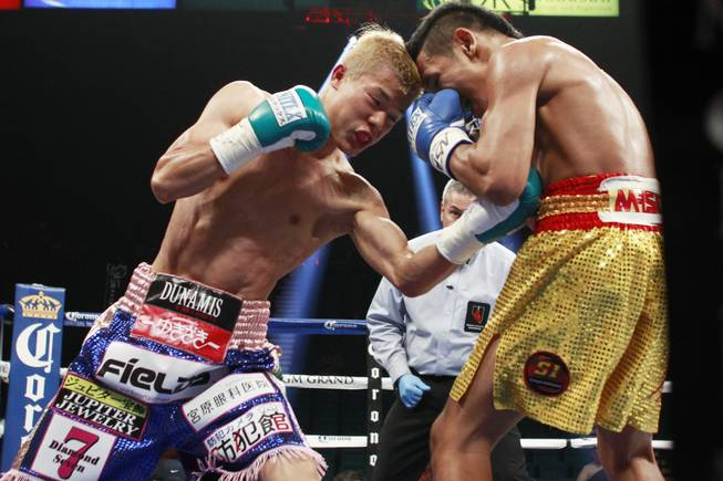 Tomoki Kameda hits Pungluang Singyu with a left to the body during their WBO bantamweight title fight Saturday, July 12, 2014 at the MGM Grand Garden Arena. Kameda won with a 7th round knock out.