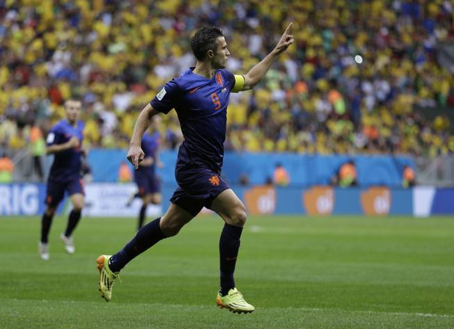 Netherlands' Robin van Persie celebrates after scoring his team's first goal on a penalty shot during the World Cup third-place soccer match between Brazil and the Netherlands at the Estadio Nacional in Brasilia, Brazil, on Saturday, July 12, 2014.