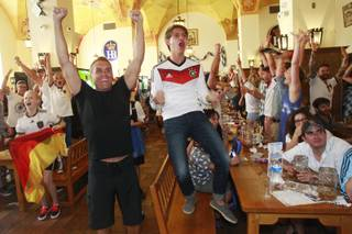 Germany fans react to their team scoring a goal in extra time while watching the World Cup final game against Argentina at the Hofbrauhaus Sunday, July 13, 2014.