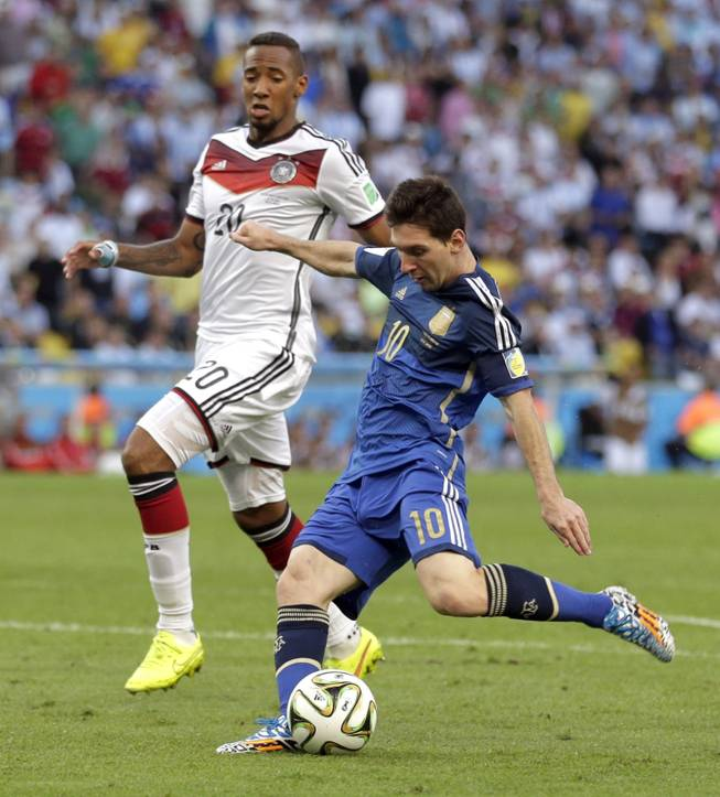 Germany's Jerome Boateng watches as Argentina's Lionel Messi takes a shot on goal during the World Cup final soccer match between Germany and Argentina at the Maracana Stadium in Rio de Janeiro, Brazil, Sunday, July 13, 2014.