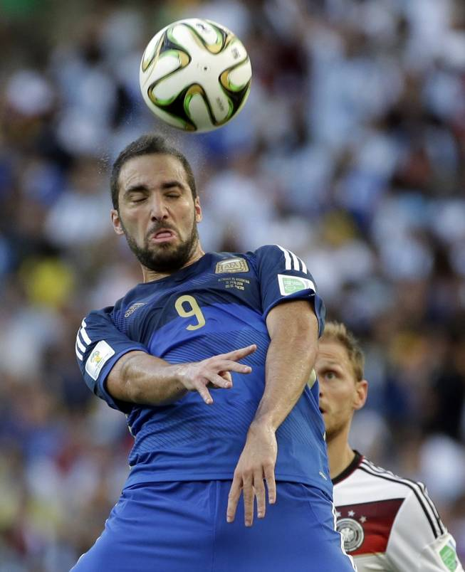 Argentina's Gonzalo Higuain heads the ball in front of Germany's Benedikt Hoewedes during the World Cup final soccer match between Germany and Argentina at the Maracana Stadium in Rio de Janeiro, Brazil, Sunday, July 13, 2014.