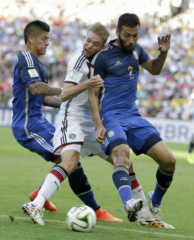 Germany's Christoph Kramer gets hit in the face by Argentina's Ezequiel Garay shoulder (2) while pinned between Garay and Marcos Rojo during the World Cup final soccer match between Germany and Argentina at the Maracana Stadium in Rio de Janeiro, Brazil, Sunday, July 13, 2014.