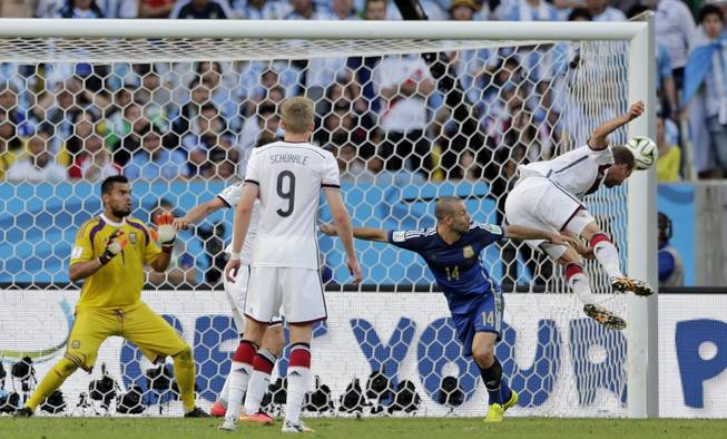 A header from Germany's Benedikt Hoewedes, right, hits the post during the World Cup final soccer match between Germany and Argentina at the Maracana Stadium in Rio de Janeiro, Brazil, Sunday, July 13, 2014.
