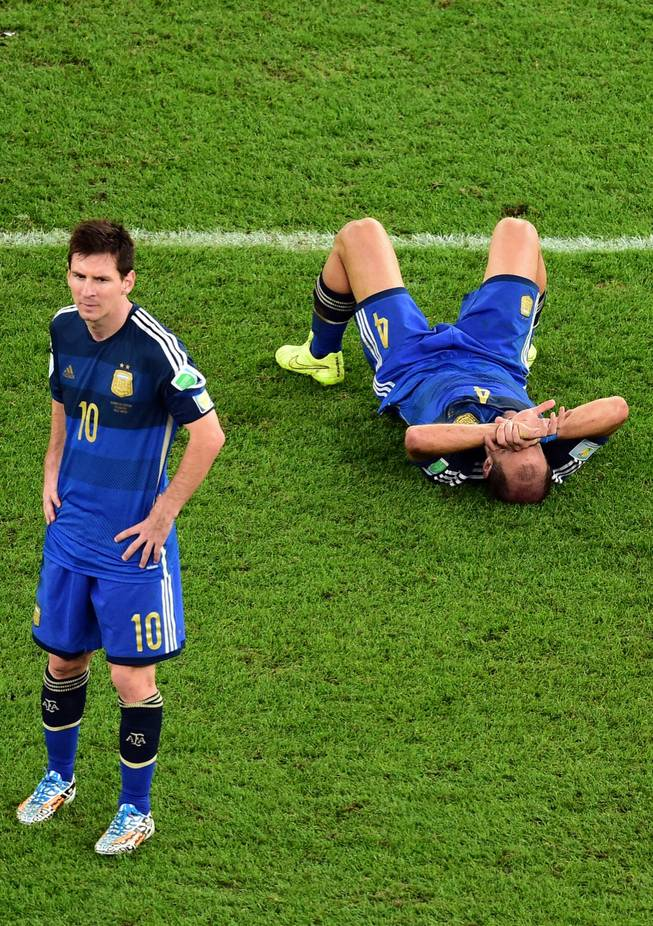 Argentina's Pablo Zabaleta lies on the pitch as Lionel Messi stands beside him after the World Cup final soccer match between Germany and Argentina at the Maracana Stadium in Rio de Janeiro, Brazil, Sunday, July 13, 2014. Mario Goetze volleyed in the winning goal in extra time to give Germany its fourth World Cup title with a 1-0 victory over Argentina on Sunday.