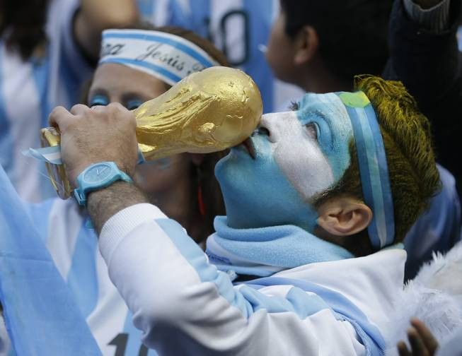 An Argentina soccer fans kisses a replica of the World Cup trophy before the World Cup final match against Germany, as he watches on an outdoor giant screen set up in Buenos Aires, Argentina, Sunday, July 13, 2014.