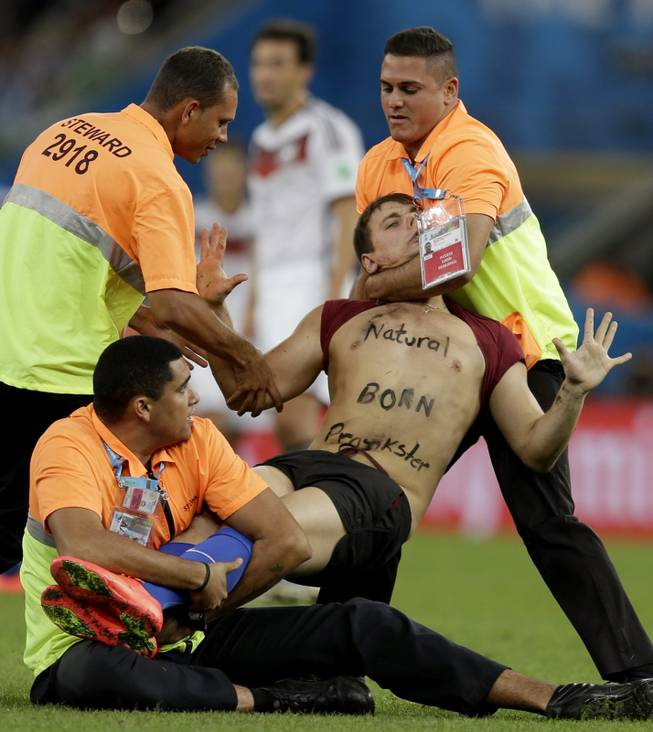 A spectator who ran on to the pitch during the World Cup final soccer match between Germany and Argentina is subdued by security personnel at the Maracana Stadium in Rio de Janeiro, Brazil, Sunday, July 13, 2014.