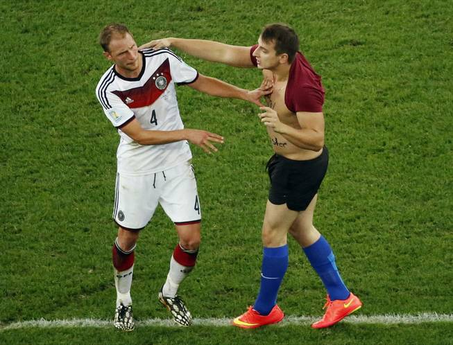 Germany's Benedikt Hoewedes faces a man who run into the pitch during the World Cup final soccer match between Germany and Argentina at the Maracana Stadium in Rio de Janeiro, Brazil, Sunday, July 13, 2014.