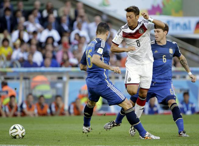 Germany's Mesut Ozil tries to get past his defenders Argentina's Martin Demichelis and Lucas Biglia (6) during the World Cup final soccer match between Germany and Argentina at the Maracana Stadium in Rio de Janeiro, Brazil, Sunday, July 13, 2014.