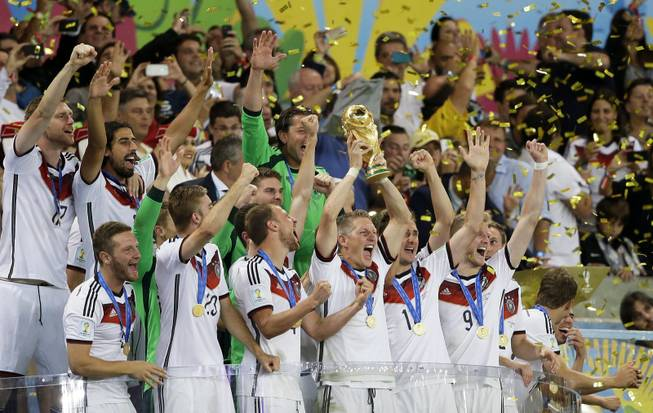 Germany's Bastian Schweinsteiger, center, lifts the trophy amid his teammates after the World Cup final soccer match between Germany and Argentina at the Maracana Stadium in Rio de Janeiro, Brazil, Sunday, July 13, 2014. Germany beat Argentina 1-0 to win the World Cup.