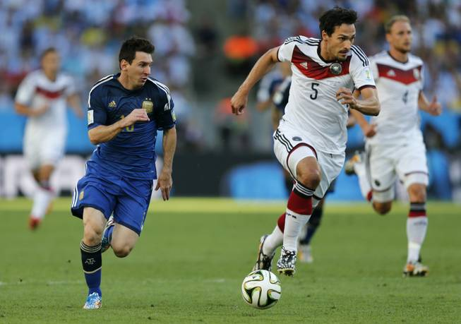 Argentina's Lionel Messi, left, and Germany's Mats Hummels go downfield during the World Cup final soccer match between Germany and Argentina at the Maracana Stadium in Rio de Janeiro, Brazil, Sunday, July 13, 2014.