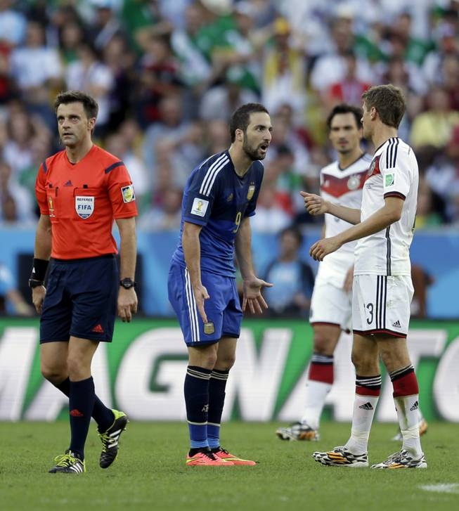 Referee Nicola Rizzoli from Italy walks away while Argentina's Gonzalo Higuain has an argument with Germany's Thomas Mueller, right, during the World Cup final soccer match between Germany and Argentina at the Maracana Stadium in Rio de Janeiro, Brazil, Sunday, July 13, 2014.