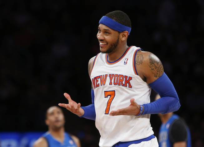 "In this Feb. 24, 2014, file photo, New York Knicks' Carmelo Anthony smiles after hitting a 3-point shot against the Dallas Mavericks during an NBA basketball game in New York. Anthony is remaining with the Knicks, saying he wants ""to stay and build here with this city and my team."" Anthony made his decision official Sunday with a posting on his website. He writes: ""In the end, I am a New York Knick at heart."""