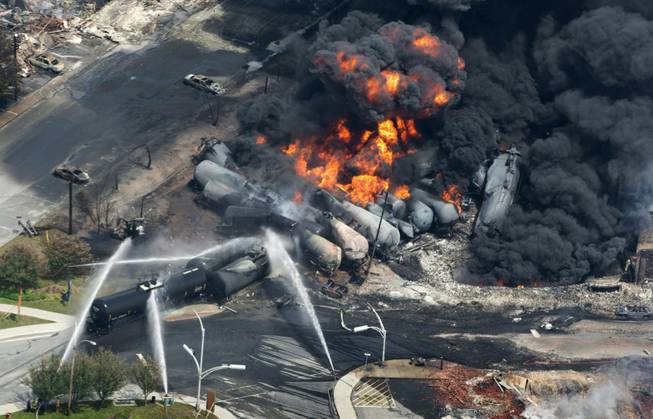 This July 6, 2013, file photo shows smoke rising from railway cars carrying crude oil after derailing in downtown Lac Megantic, Quebec. A string of fiery train derailments across the country has triggered a high-stakes and behind-the-scenes campaign to shape how the government responds to calls for tighter safety rules. Billions of dollars are riding on how these rules are written, and lobbyists from the railroads, tank car manufacturers and the oil, ethanol and chemical industries have met more than a dozen times since mid-May 2014 with officials at the White House and the Pipeline and Hazardous Materials Safety Administration. Their universal message: Don't make us pay for increased safety — that's another industry's problem.